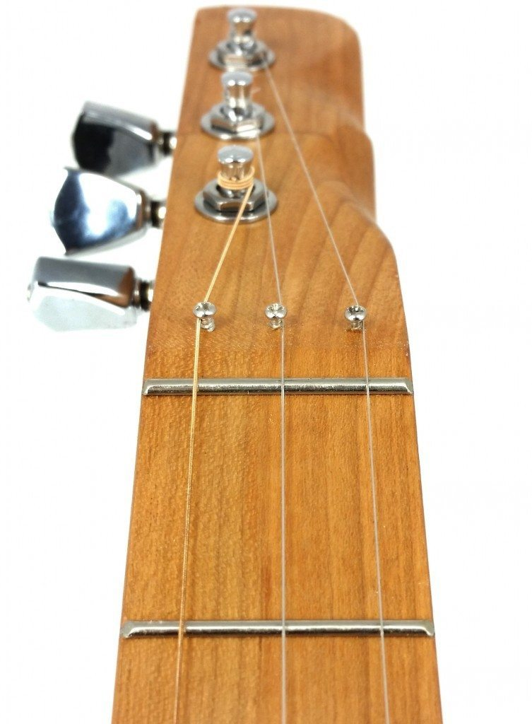 Here is another angle of a zero fret installed on a cigar box guitar. This particular guitar featured an angled headstock, so the retainer screws are just holding the strings in the correct position, not holding them down to increase break angle.