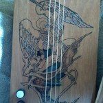 Biblical-based sound hole and engraving in a cigar box guitar by James Cissell.