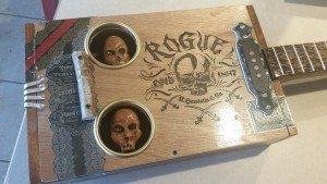Spooky inset skull sound holes in a cigar box guitar by Jeff Cox.