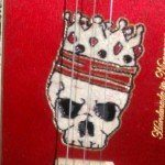 A hand-carved (with an Xacto knife) Skull & Crown sound hole design on a cigar box guitar, by Piht Bull.