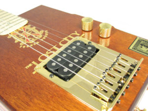 This electric cigar box guitar features a bottom-loading gold hard-tail bridge with humbucker opening.